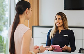 Woman checking in at dental office reception desk