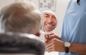Man looking at smile after metal free dental restoration