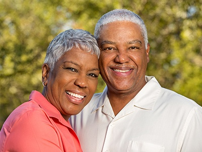 Older man and woman with dentures smiling