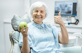 Older woman with dental implant retained dentures holding up a green apple and giving thumbs up