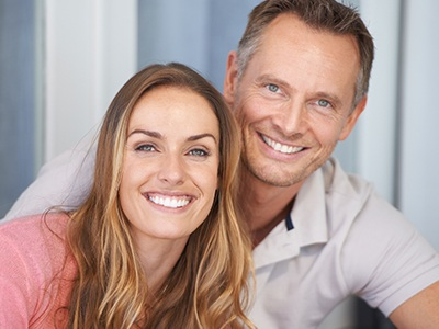 Man and woman smiling after emergency dentistry treatment
