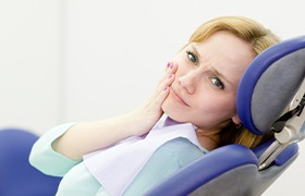 Woman in dental chair holding cheek before emergency dentistry treatment