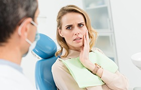 Woman in dental chair holding cheek during emergency dentistry