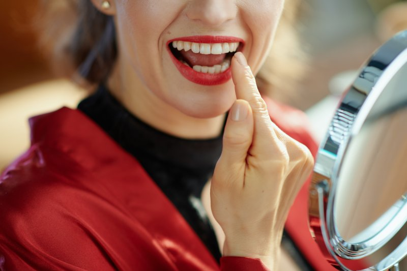 Woman smiling after seeing cosmetic dentist